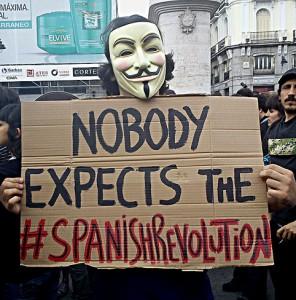 """Anonymous sosteniendo un cartel que dice """"Nobody expects the #SpanishRevolution"""" en la plaza del Sol de Madrid, España."""